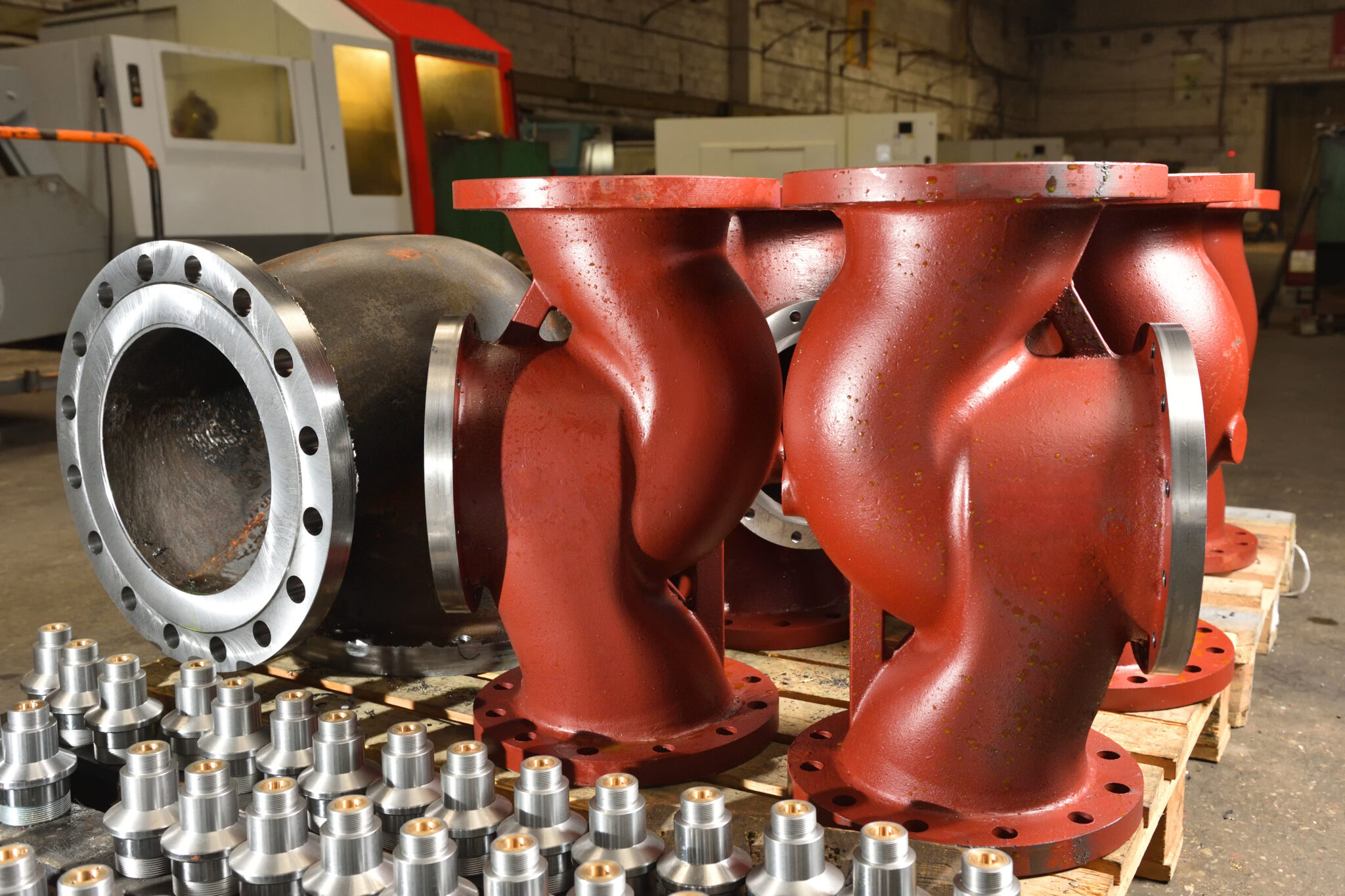 Large iron or cast iron pipes, bases for creating valves, lie on a wooden panel before further processing on a milling machine. Red bases to create valves in the factory